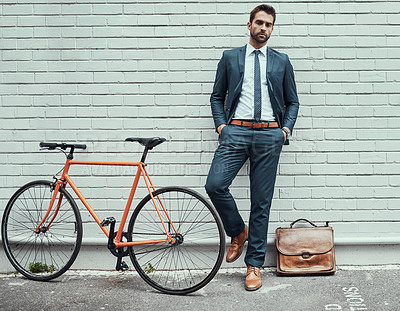 Buy stock photo Portrait of a handsome young businessman standing alongside his bike outdoors