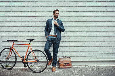 Buy stock photo Shot of a handsome young businessman standing alongside his bike outdoors