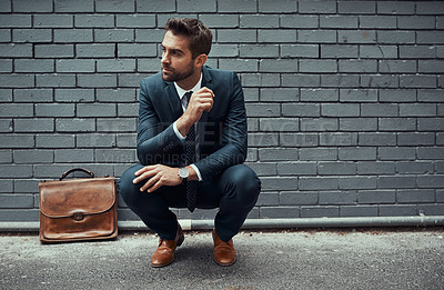 Buy stock photo Shot of a handsome young businessman posing against a grey wall outdoors