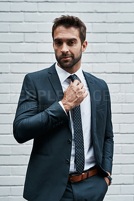 Buy stock photo Portrait of a handsome young businessman posing against a white wall outdoors