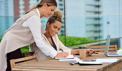 Buy stock photo Cropped shot of an attractive young businesswoman helping out a female colleague in the office