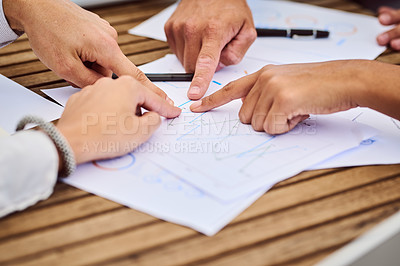 Buy stock photo Cropped shot of a group of unrecognizable businesspeople pointing at paperwork during a meeting in the boardroom