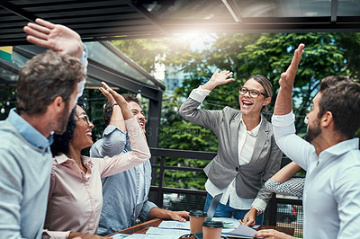 Buy stock photo Shot of a group of colleagues high fiving during a meeting at a cafe