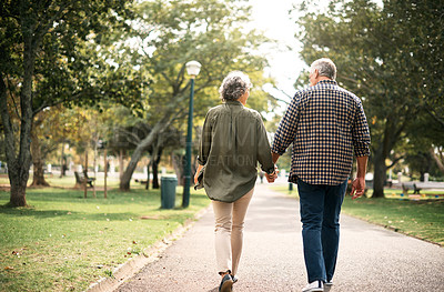Buy stock photo Rearview shot of a senior couple going for a walk in the park