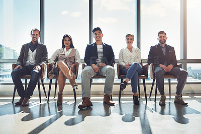 Buy stock photo Portrait of a group of businesspeople sitting in line in an office