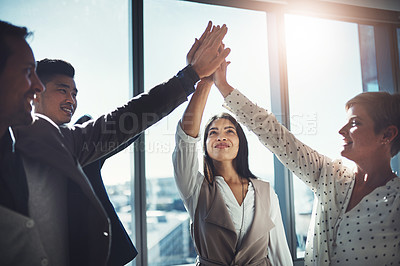 Buy stock photo Shot of a diverse group of businesspeople high fiving in an office