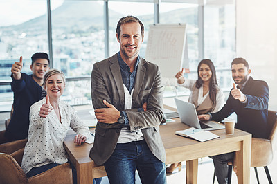 Buy stock photo Portrait of a mature businessman standing in an office with his colleagues showing thumbs up in the background