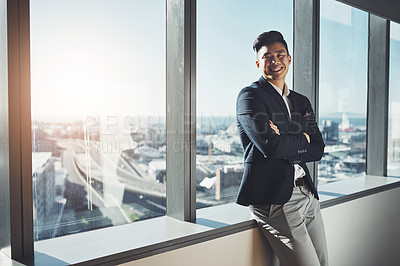 Buy stock photo Portrait of a young businessman standing at a window in an office