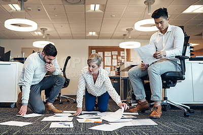 Buy stock photo Shot of businesspeople working on paperwork together on the floor in the office