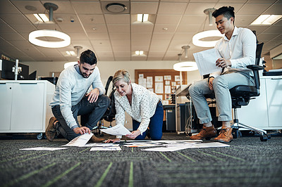 Buy stock photo Shot of businesspeople working with paperwork together on the floor in the office