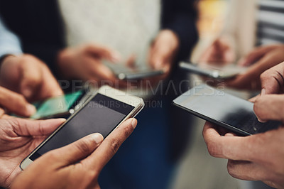 Buy stock photo Closeup shot of an unrecognizable group of businesspeople using their cellphones in synchronicity