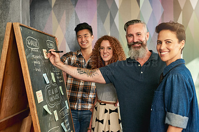 Buy stock photo Cropped shot of creative colleagues brainstorming at a blackboard in a modern office