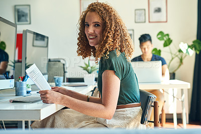 Buy stock photo Cropped portrait of an attractive young female designer reading over some paperwork in the office