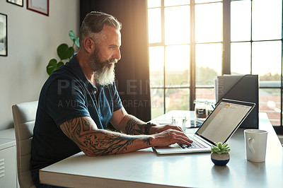 Buy stock photo Cropped shot of a handsome mature businessman working on his laptop in the office