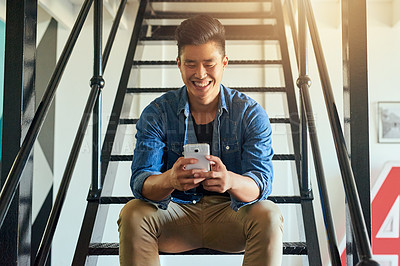 Buy stock photo Cropped shot of a handsome young male designer sending a text message in the office
