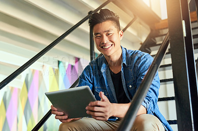 Buy stock photo Cropped portrait of a handsome young male designer working on a tablet in his office
