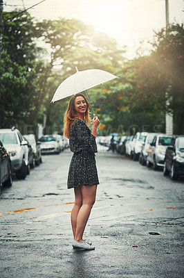 Buy stock photo Shot of a beautiful young woman walking in the rain outside