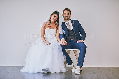 Buy stock photo Studio portrait of a newly married young couple sitting together against a gray background