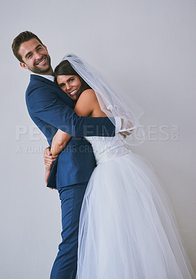 Buy stock photo Studio portrait of a newly married young couple hugging a gray background
