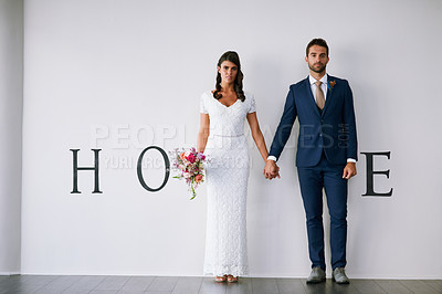 """Buy stock photo Concept studio portrait of a bride and groom making an M in the word """"home"""" against a wall"""