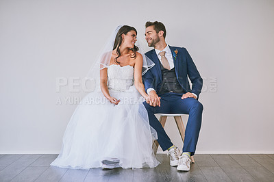 Buy stock photo Studio shot of a newly married young couple sitting together against a gray background