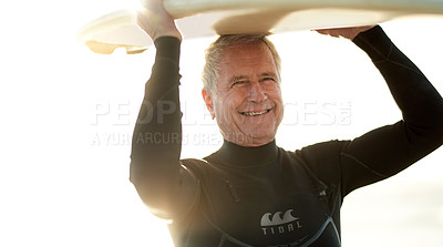 Buy stock photo Cropped shot of a senior man holding a surfboard on top of his head on his way to go surfing