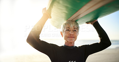 Buy stock photo Cropped shot of a senior woman holding a surfboard on top of her head on her way to go surfing