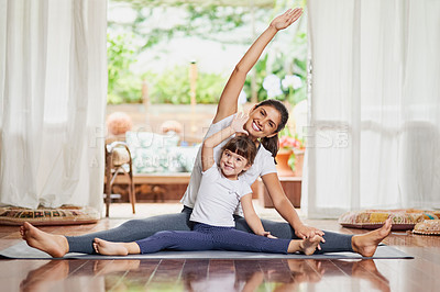 Buy stock photo Portrait of a cheerful young mother and daughter doing a yoga pose together while stretching their arms to the side