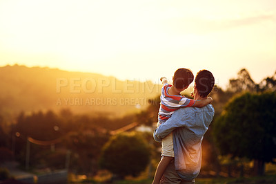 Buy stock photo Rearview shot of a little boy pointing at something to his father outdoors