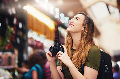 Buy stock photo Shot of a cheerful young woman taking photos of market stalls at a busy bazaar outside during the day
