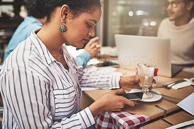 Buy stock photo Shot of a focused young woman texting on her cellphone while being seated at a coffeeshop drinking a hot beverage