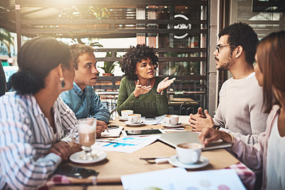 Buy stock photo Shot of a group of focused young work colleagues having a discussion at a meeting together while being seated around a table