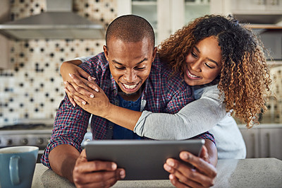 Buy stock photo Cropped shot of an affectionate young couple using a tablet in their kitchen at home