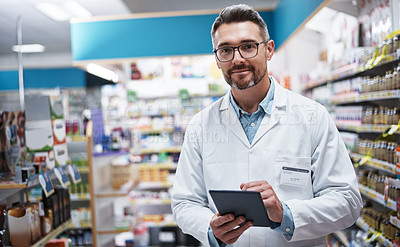 Buy stock photo Portrait of a handsome mature pharmacist using a digital tablet in a pharmacy