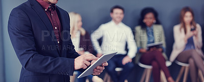 Buy stock photo Cropped shot of an unrecognizable businessman using a tablet with his colleagues in the background