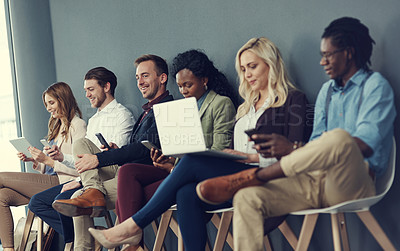 Buy stock photo Shot of a group of businesspeople using different wireless devices while waiting in line for an interview