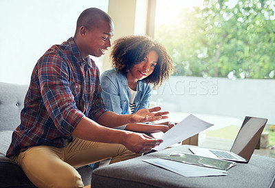 Buy stock photo Shot of a cheerful young couple working on a laptop and doing paperwork together while being seated on a couch at home