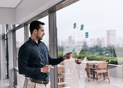 Buy stock photo Shot of a young businessman writing on a glass wall in an office