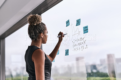 Buy stock photo Shot of a young businesswoman writing on a glass wall in an office