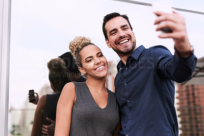 Buy stock photo Shot of two colleagues taking a selfie together outside an office