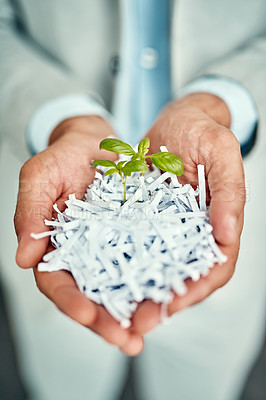 Buy stock photo High angle shot of an unrecognizable businessman holding a budding flower in shredded paper in his office