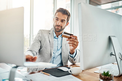 Buy stock photo Shot of a handsome young businessman using a computer while holding a credit card in an office