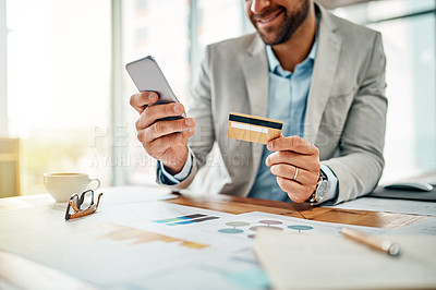 Buy stock photo Closeup shot of an unrecognizable businessman using a cellphone while holding a credit card in an office