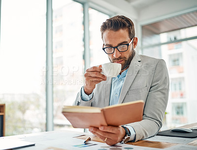 Buy stock photo Shot of a handsome young businessman drinking coffee while reading a book in an office