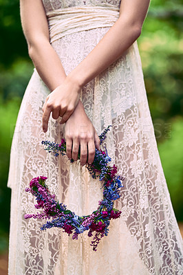 Buy stock photo Cropped shot of an unrecognizable woman holding a floral head wreath posing in nature