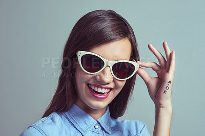 Buy stock photo Studio portrait of an attractive young woman posing with with stylish shades against a grey background