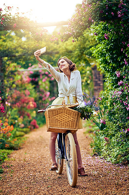 Buy stock photo Shot of an attractive young woman taking a selfie while riding a bicycle outdoors