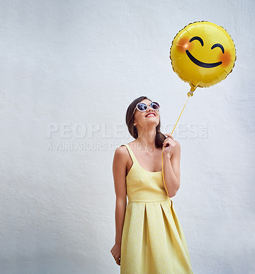Buy stock photo Studio shot of a cheerful young woman holding a smiling emoticon balloon while standing against a grey background