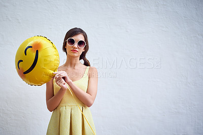 Buy stock photo Studio portrait of a confident young woman holding a smiling emoticon balloon while standing against a grey background