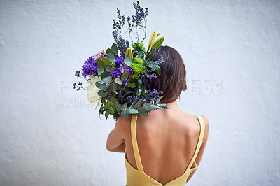 Buy stock photo Rearview studio shot of an unrecognizable woman holding a bouquet of flowers while standing against a grey background